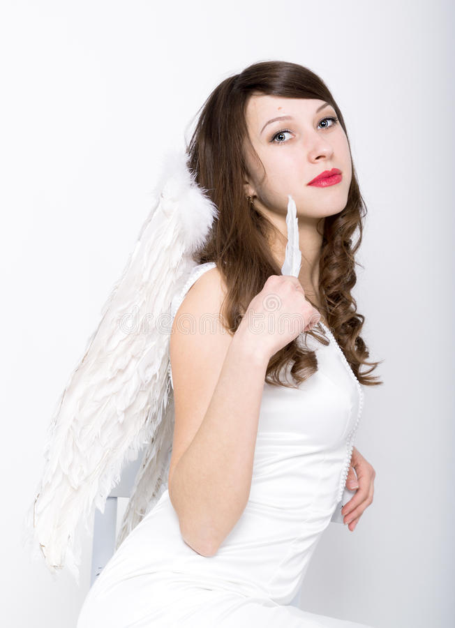 Härlig sexig slank kvinna i lite den vita klänningen med vingar bak henne royaltyfri fotografi