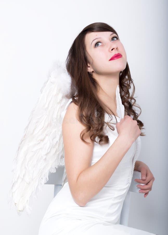 Härlig sexig slank kvinna i lite den vita klänningen med vingar bak henne royaltyfria foton