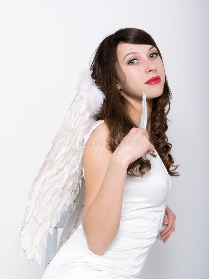 Härlig sexig slank kvinna i lite den vita klänningen med vingar bak henne arkivbilder