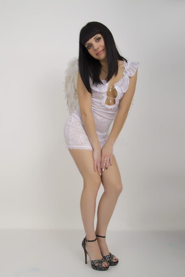 Härlig sexig slank kvinna i lite den vita klänningen med vingar bak henne arkivbild