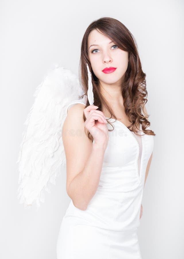 Härlig sexig slank kvinna i lite den vita klänningen med vingar bak henne och att rymma en fjäder arkivbild