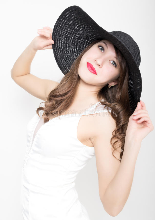 Härlig sexig slank kvinna i lite den vita klänningen och bred svart hatt royaltyfria foton