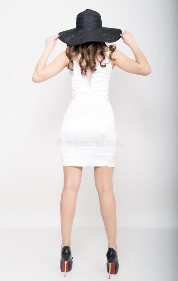 Härlig sexig slank kvinna i lite den vita klänningen och bred svart hatt royaltyfria bilder