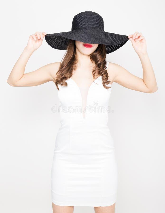 Härlig sexig slank kvinna i lite den vita klänningen och bred svart hatt royaltyfri foto