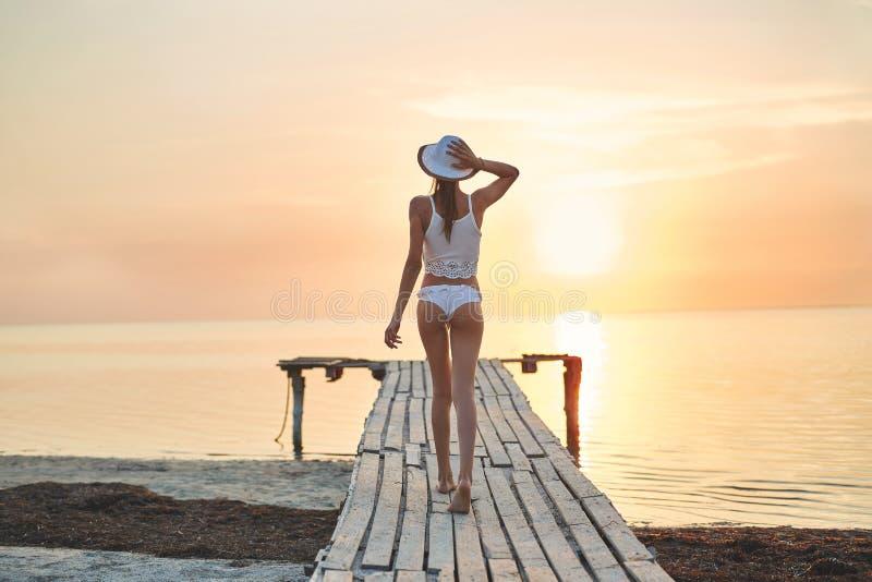 Härlig sexuell kvinna i den vita hatten och bikinin på en träpir mot havet och solnedgången arkivfoto