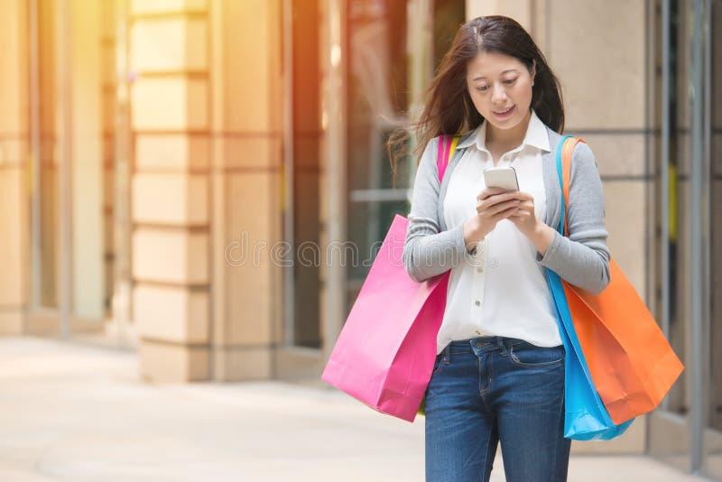 Härlig shoppingkvinna som använder den smarta telefonen arkivbilder