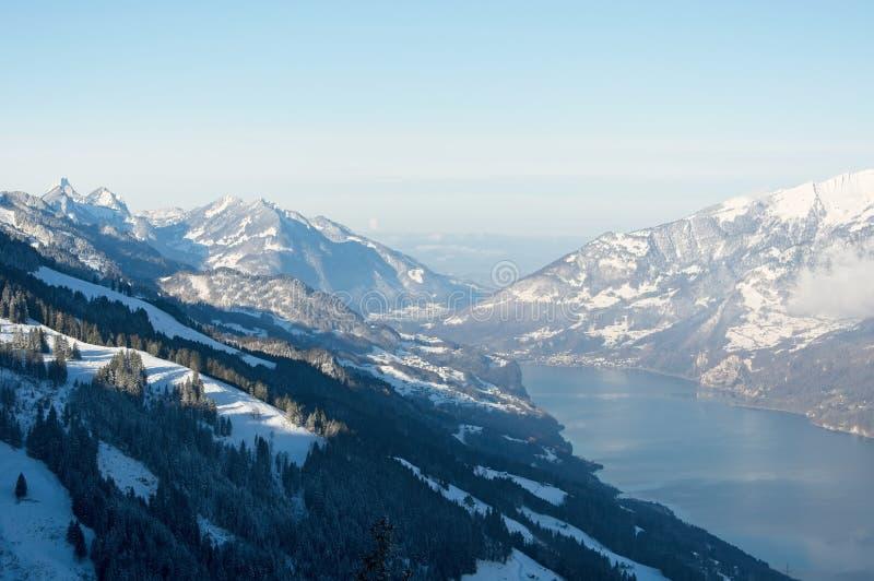 Härlig sikt av de snöig bergen och en sjö på en solig vinterdag fotografering för bildbyråer