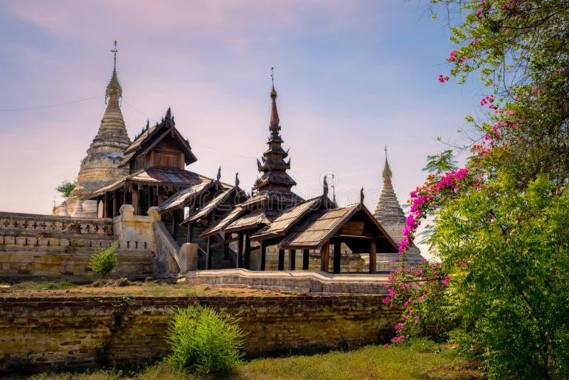 Härlig sikt av den forntida templet i gamla Bagan med blommaförgrund royaltyfria bilder