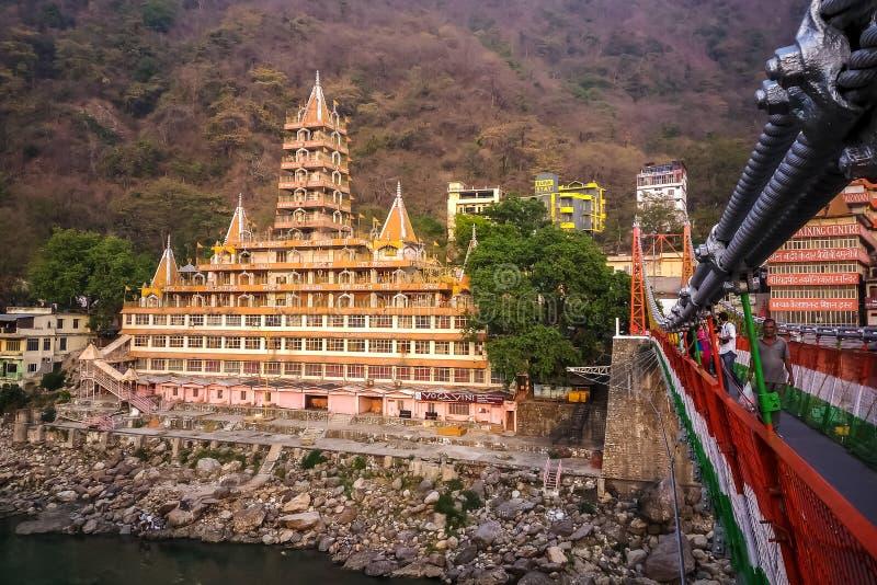 Härlig sikt av den Ganga flodinvallningen, den Lakshman Jhula bron och Tera Manzil Temple, Trimbakeshwar i Rishikesh, Indien arkivbild