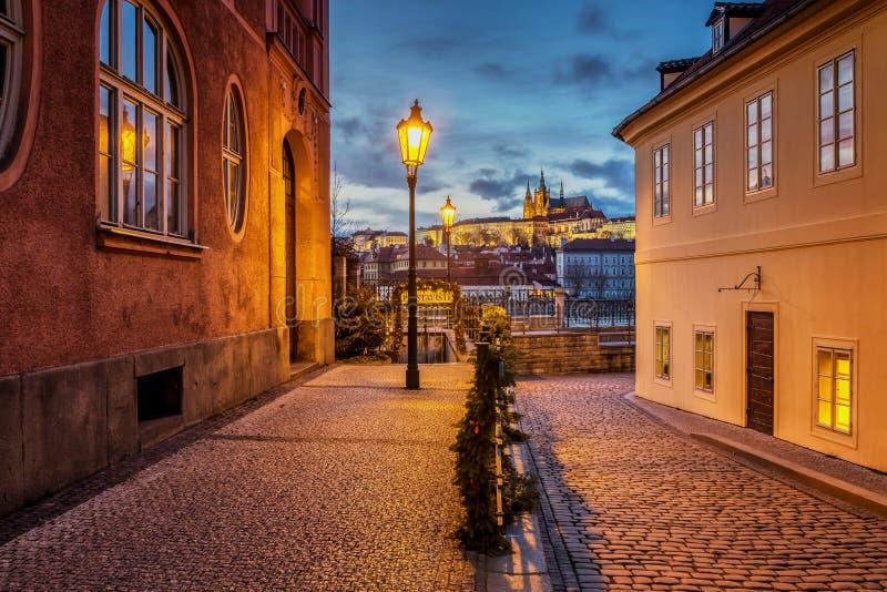 Härlig sikt av den Prague slotten på solnedgången från en historisk gata med gaslampor över floden Vltava royaltyfri fotografi