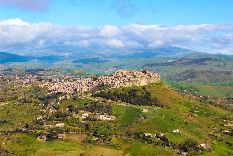 Härlig sikt av den Sicilian byn Calascibetta som tas med närgränsande berg och grönt landskap Den historiska arabiska staden royaltyfria bilder