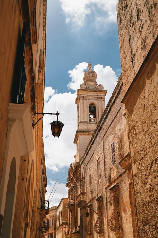 Härlig sikt av den smala medeltida gatan i Mdina med det Carmelite kyrkaKlocka tornet en blå himmel med moln på bakgrunden arkivbild