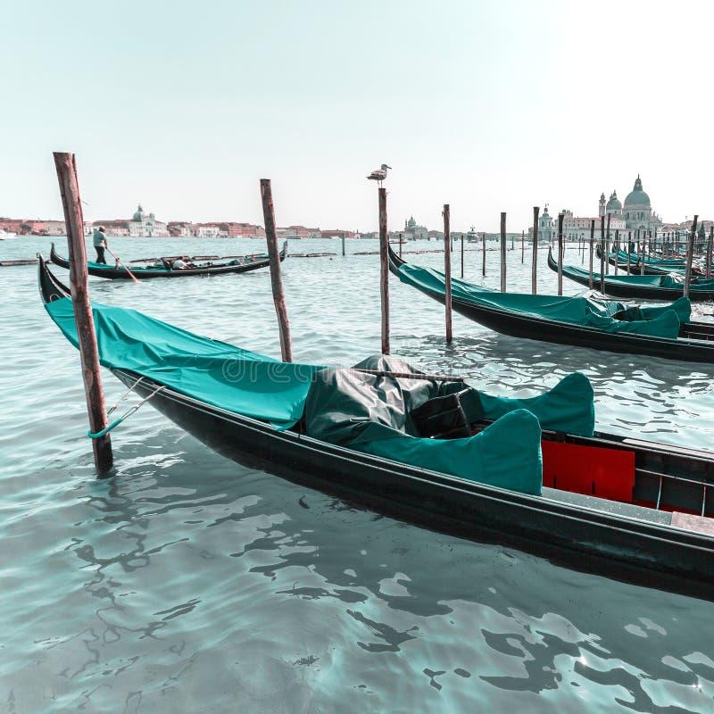 Härlig sikt av den traditionella gondolen på kanalen som är stor med basilikadi Santa Maria della Salute i Venedig, Italien arkivbild