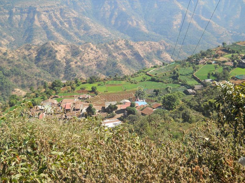 Härlig sikt av en liten by ner från över en välkänd kullestation arkivbild