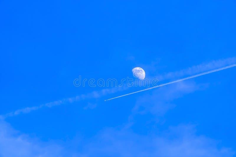 Härlig sikt av en måne fortfarande som är synlig på den vibrerande blåa himlen under dag arkivbild