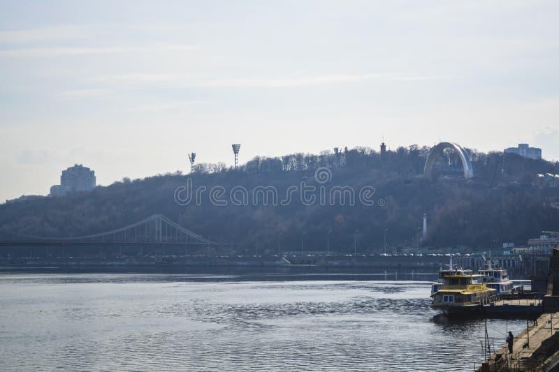 Härlig sikt av floden och av Kiev, Ukraina solig dagfjäder Broar och stadsarkitektur Landskap royaltyfri bild