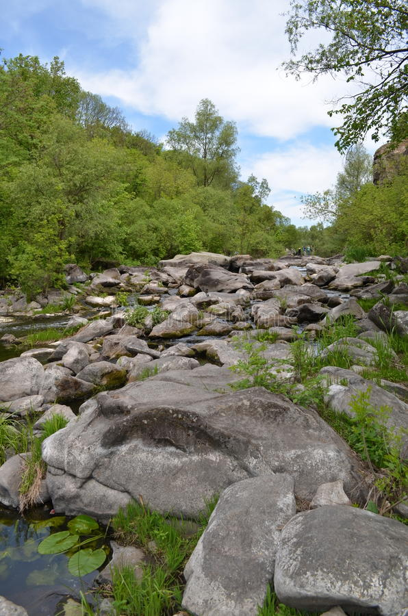 Härlig sikt av granitstenar i den lilla och snabba floden royaltyfri bild