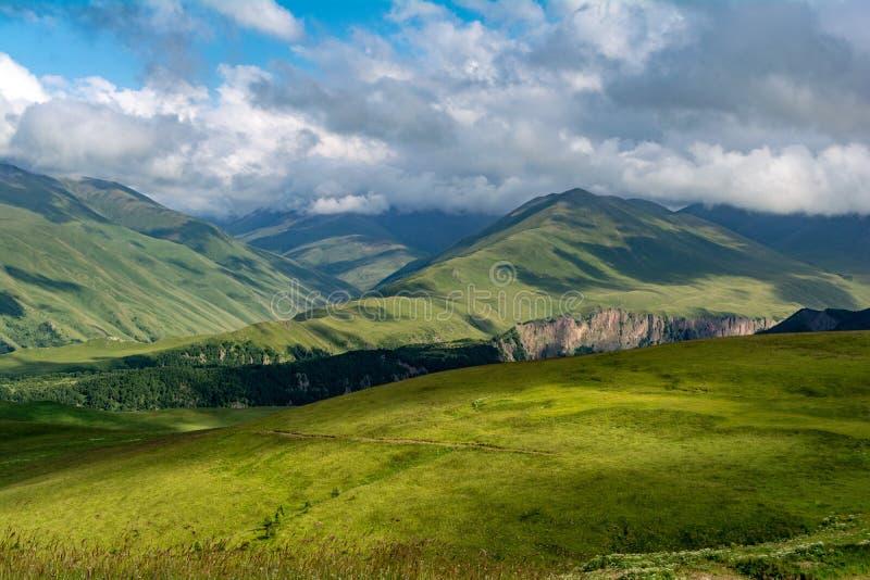 Härlig sikt av idylliskt alpint berglandskap med att blomma ängar och berg på en härlig solig dag med blå himmel och arkivbilder