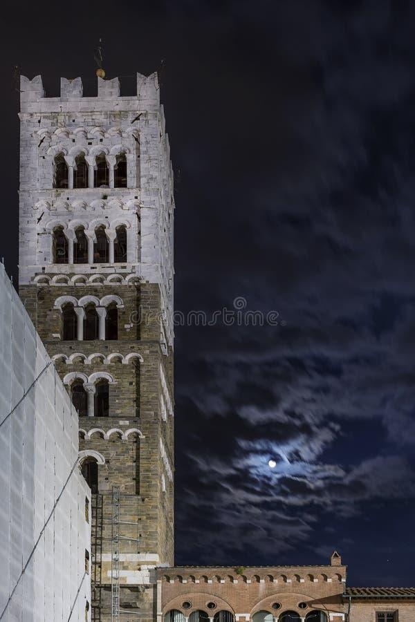 Härlig sikt av klockatornet av duomoen av San Martino med månen och molnen i natthimlen, Lucca, Tuscany, Italien arkivfoto