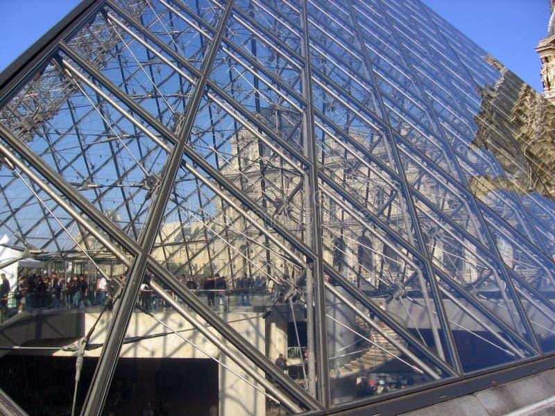 Härlig sikt av Louvre - pyramiden glasade trappa och folk som inom genomreser royaltyfria foton