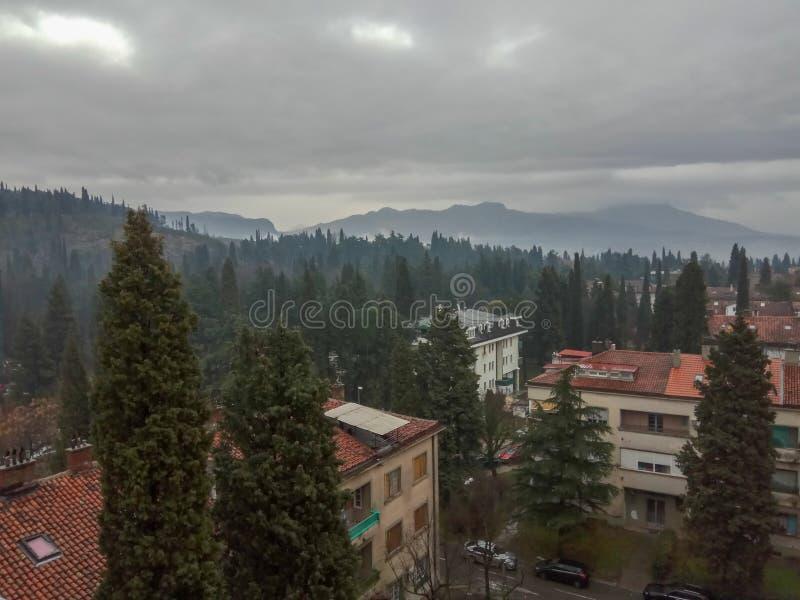 Härlig sikt av staden på foten av de gröna dimmiga bergen mot molnig himmel royaltyfri fotografi