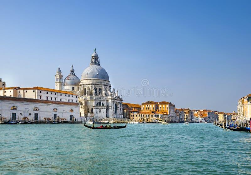 Härlig sikt av traditionella gondoler på kanalen som är stor med historiska basilikadi Santa Maria della Salute i bakgrunden på e arkivfoto