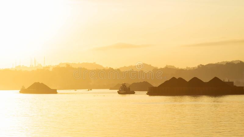 Härlig sikt av trafik av bogserbåtar som drar pråm av kol på den Mahakam floden, Samarinda, Indonesien royaltyfri foto