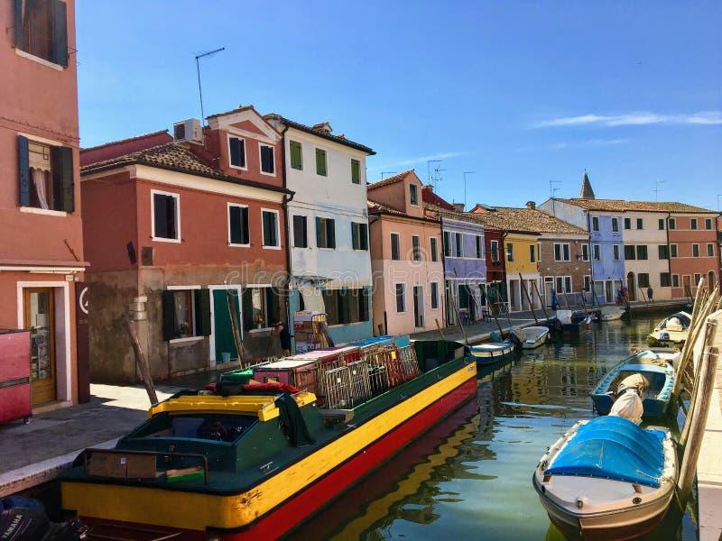härlig sikt för solig dag av en kanal i Burano, Italien med färgglade gamla fyrkantiga hem som fodrar kanalen, tillsammans med en fotografering för bildbyråer