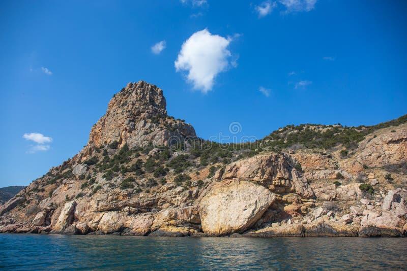 Härlig sikt från vatten på det gula och orange Crimean berglandskapet nära Balaklava på loppet och resan för sommar för havskust royaltyfri bild