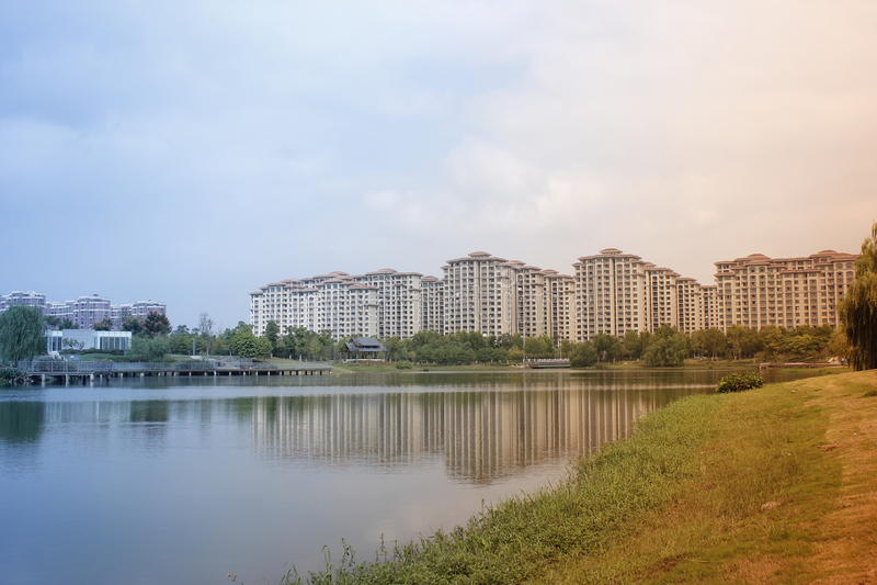 Härlig sikt med byggnader som reflekterar på sjön som nära hemstaden royaltyfria bilder