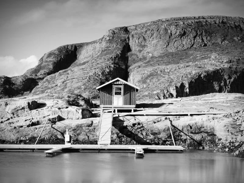 Härlig sikt på den norska fjärden med traditionella hus längs den steniga kustlinjen Vår Norge royaltyfri bild
