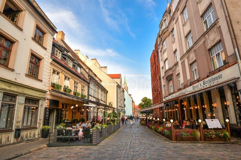 Härlig sikt på gamla färgrika byggnader och gatakaféer av Riga, Lettland SommarRiga centrum och gåfolk royaltyfri foto