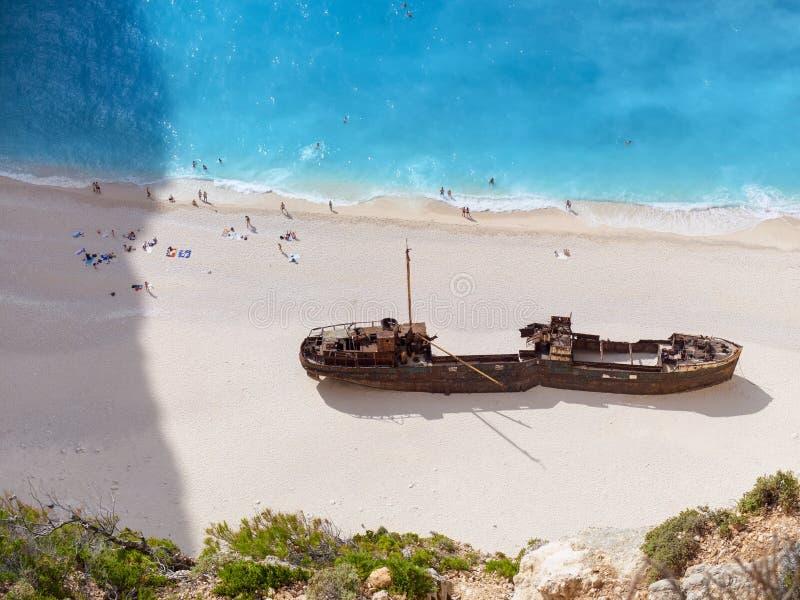 Härlig sikt på skeppsbrottstranden i fantastisk fjärd, fartyg och skepp med simningfolk i blått vatten för Ionian hav Zakynthos ö royaltyfri bild