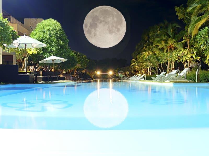Härlig simbassäng på nattsikten med fullmåneparaplyet och stol omkring royaltyfria foton