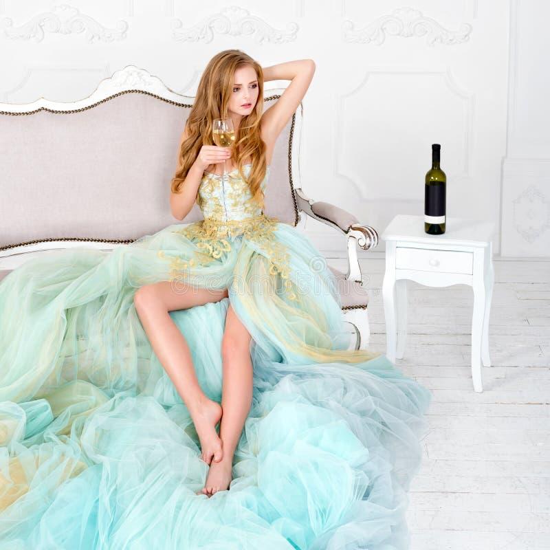 Härlig sinnlig blond kvinna i hållande exponeringsglas för ursnygg lång klänning av vitt vin med flaskanseende på tabellen arkivbilder