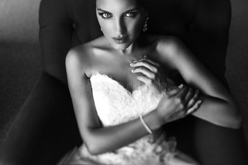 Härlig sinnlig brunettbrud i vitt klänningsammanträde på leath royaltyfri fotografi