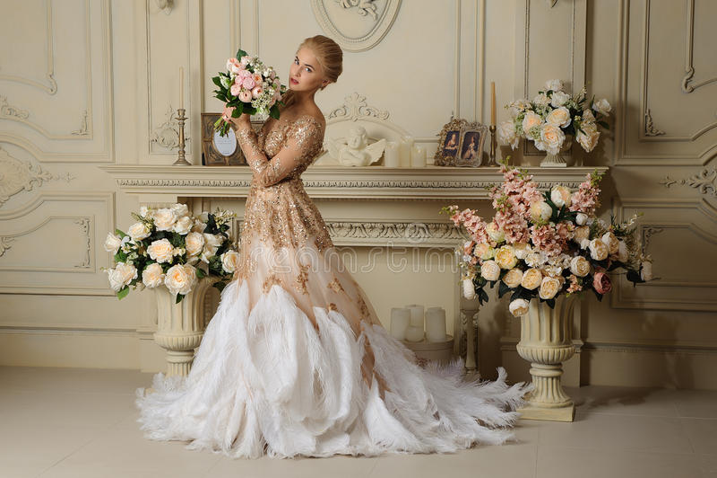 Härlig sinnlig flickablondin i beige klänning i retro inre royaltyfri foto