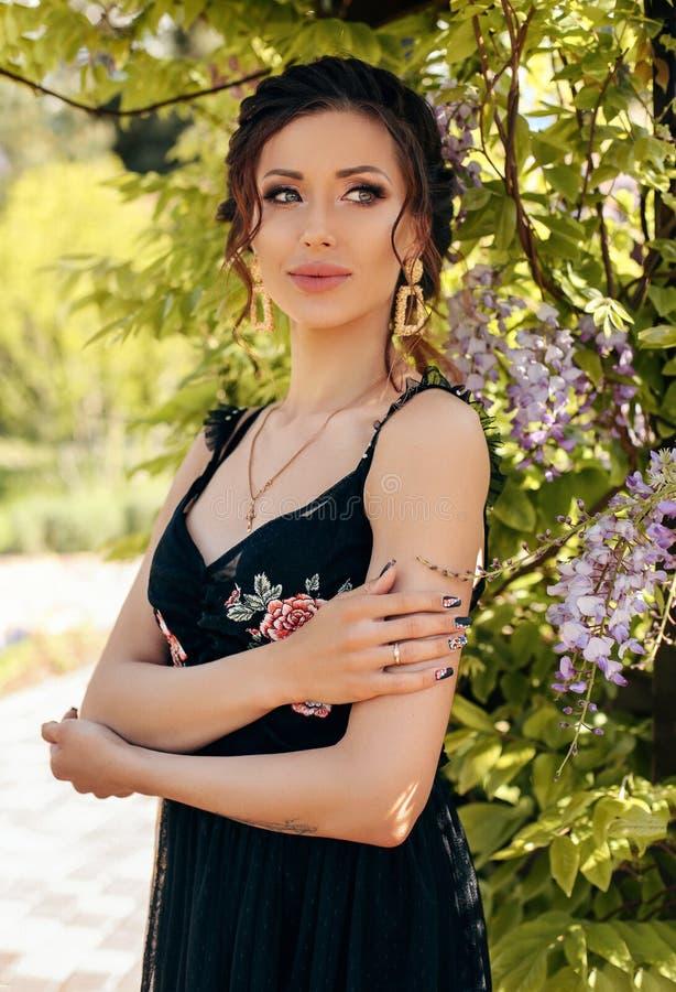 Härlig sinnlig kvinna med mörkt hår i elegant kläder som poserar i trädgård med blomningwisteriaträd arkivfoto