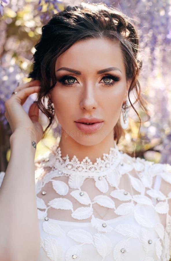 Härlig sinnlig kvinna med mörkt hår i elegant kläder som poserar i trädgård med blomningwisteriaträd royaltyfria bilder