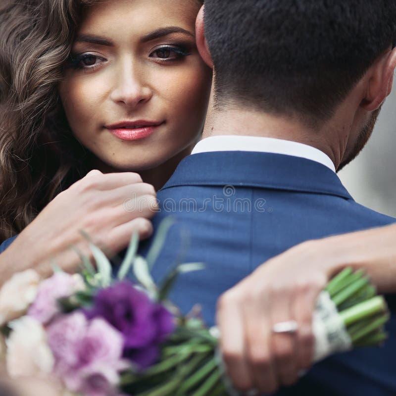 Härlig sinnlig nygift personbrud som kramar den stiliga brudgumframsidan arkivfoton
