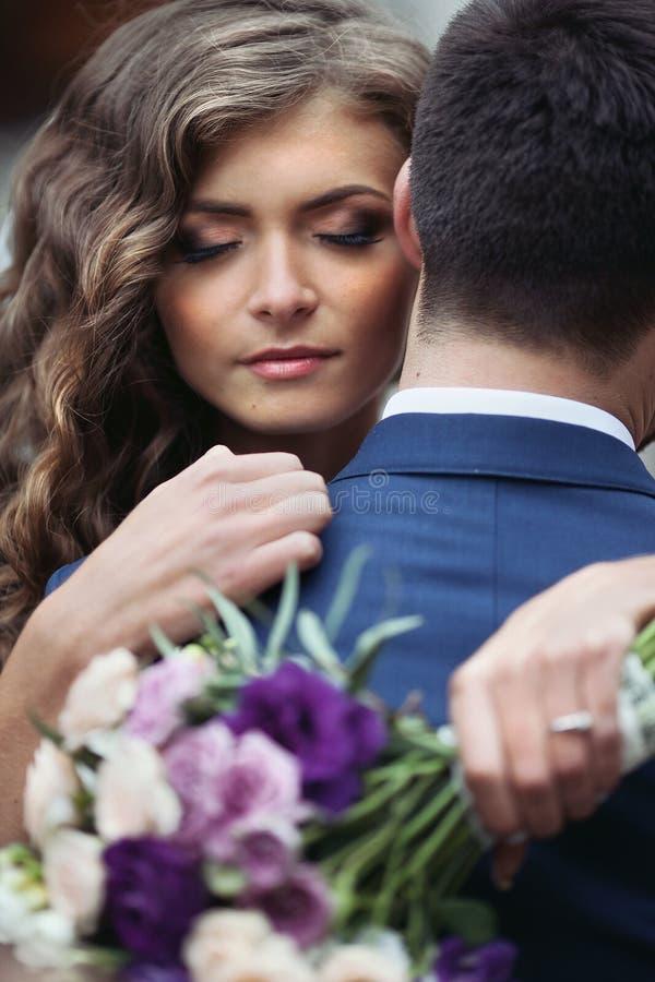 Härlig sinnlig nygift personbrud som kramar stiliga brudgumframsidaclo royaltyfri bild
