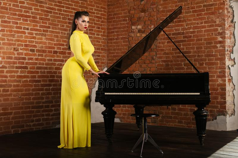 Härlig sinnlig och sexig blond flicka i ett gult klänninganseende nära pianot arkivfoto