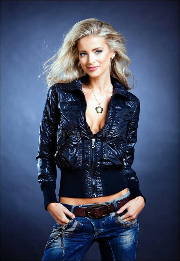 Härlig sinnlig sexig blond flicka med blåa ögon i ett läder j arkivfoto