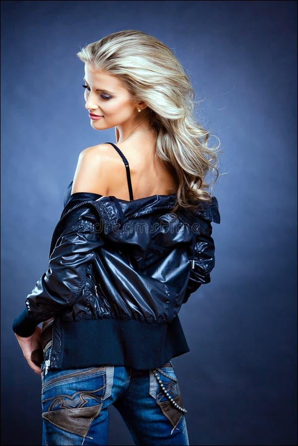 Härlig sinnlig sexig flickablondin i ett läderomslag på en blått royaltyfria bilder