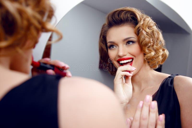 Härlig sinnlig ung kvinna som applicerar röd läppstift på kanter som ser spegeln Den härliga kvinnan gör aftonmakeup fotografering för bildbyråer