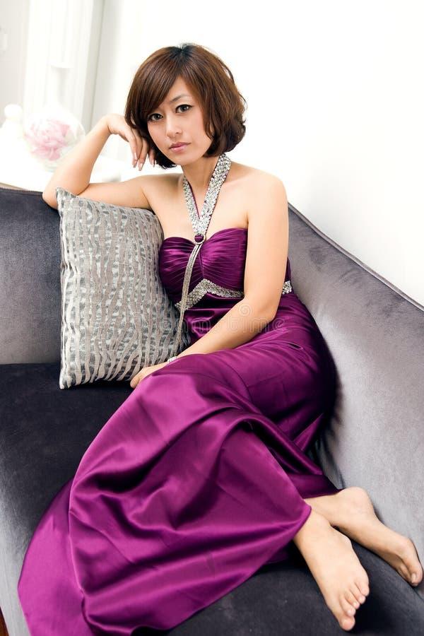 härlig sittande sofakvinna royaltyfria bilder