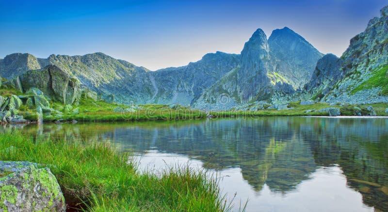 Härlig sjö med bergreflexion i Retezat, Rumänien arkivfoton