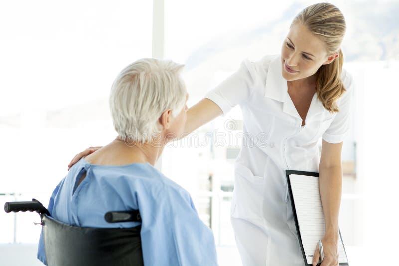Härlig sjuksköterska som att bry sig den höga patienten som sitter på rullstolen på sjukhuset arkivfoton