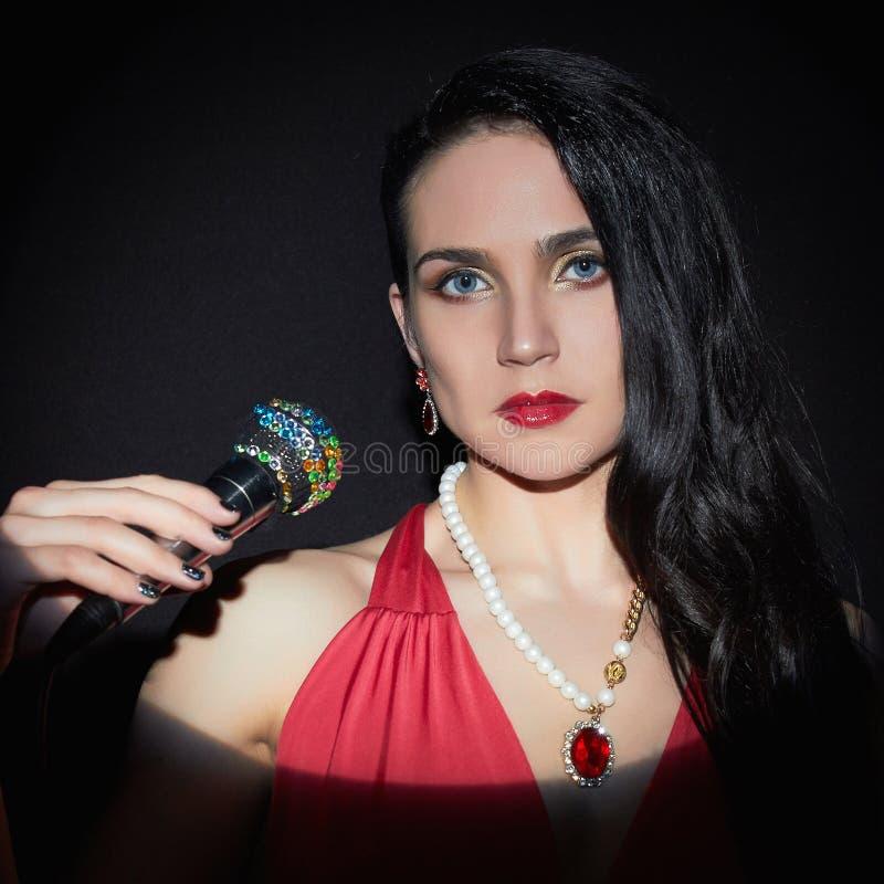 Härlig sjungande kvinna med mikrofonen royaltyfri foto