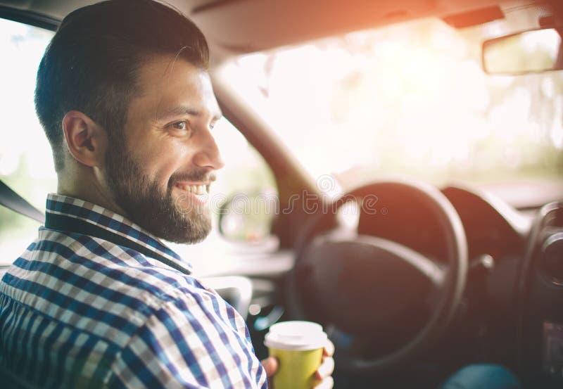 Härlig skäggig man som ler, medan att sitta på de främre passagerareplatserna i bilen och henne är att dricka kaffe från a royaltyfria foton